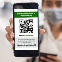 Traveler,Shows,Health,Passport,Of,Vaccination,Certification,On,Phone,At